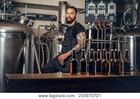Black Bearded Tattooed Hipster Male Manufacturer Presenting Craft Beer In The Microbrewery.
