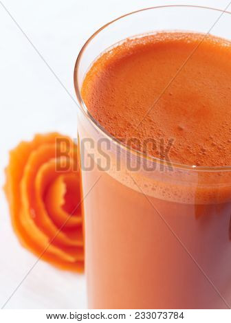 A Glass Of Carrot Juice Close Up With A Carrot Flower In The Background