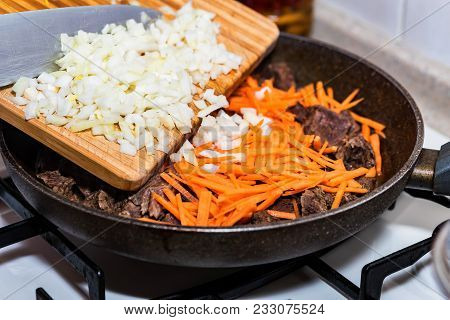 Close-up Adding Chopped Onion On Frying Pan With Beef Stew