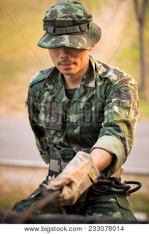 Closeup Soldier Training Rappel With Rope. Military Man Does Hanging On Climbing Equipment.