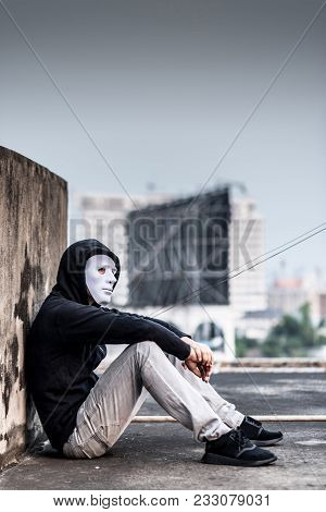 Mystery Man In White Mask With Hoody Jacket, Sitting Thinking Of Something With Sad Eyes. Depression