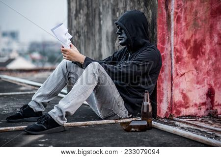 Mystery Man Wearing Black Mask And Hoody Jacket Looking At White Mask On His Hand, Depression Self D