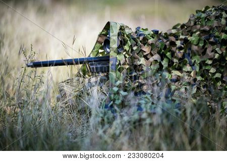 Sniper Laying On The Grass Looking Through Scope At The Target