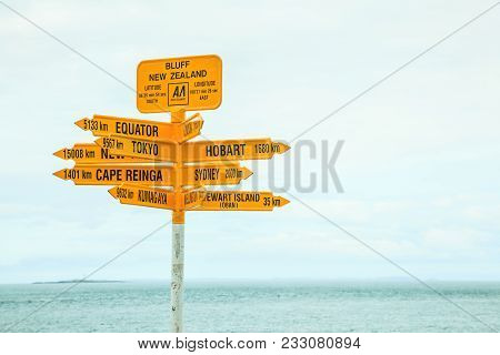 Bluff New Zealand Yellow Signpost, With Arrows Pointing To Different Directions, Major Destinations,