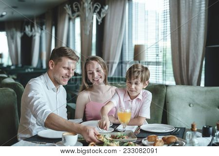 Happy family with a child dining in a restaurant