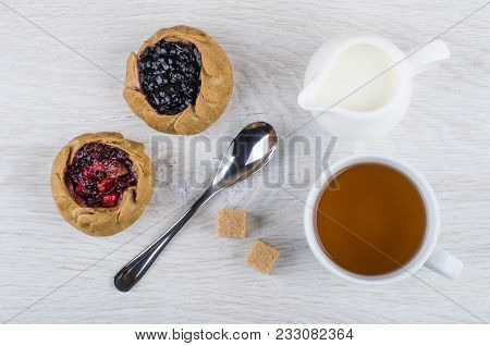 Pies With Blueberries, Cowberries, Jug Of Milk, Tea In Cup, Sugar And Spoon On Wooden Table. Top Vie