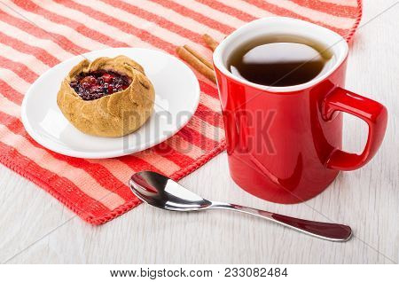 Pie With Cowberries In Saucer, Cinnamon On Striped Napkin, Cup Of Tea, Teaspoon On Wooden Table