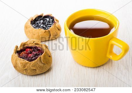 Pies With Blueberries, Cowberries, Tea In Yellow Cup On Wooden Table
