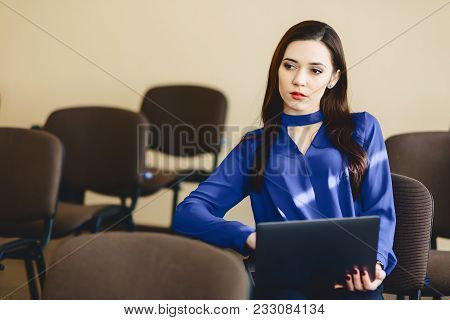 Girl In Auditorium Works With Laptop On Hands