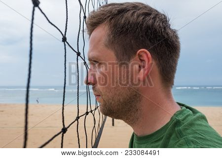 Portrait Of Caucasian Man Standing Near The Volleyball Net And Looking Aside Waiting For Start Of Ga