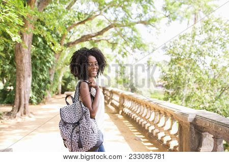Side View Of Smiling Black Woman With Backpack In City Park. Afro American Tourist Traveling Alone A