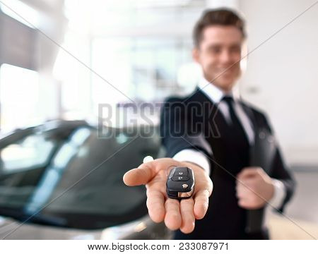 Formal Wearing Young Salesman Offers Brand New Car Key. Close Up Of The Key In The Foreground. Focus