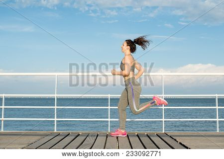 Happy Latin Fit Girl Running Alone On Bridge. Student In Tracksuit Keeping Fit And Enjoying Availabl