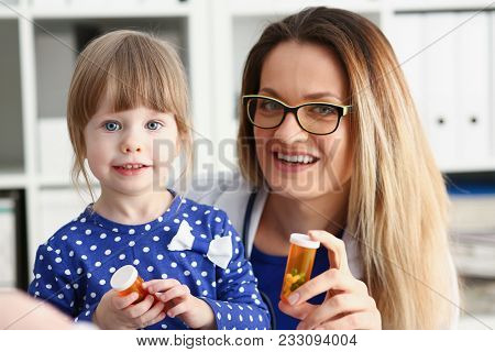 Beautiful Smiling Female Doctor Hold In Arms Pill Bottle And Offer It To Child Visitor Closeup. Pana