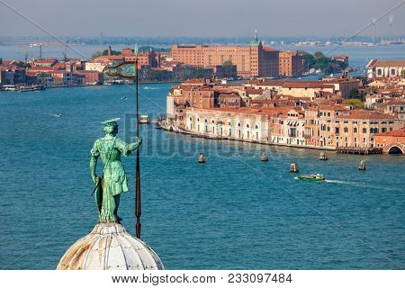 Sculpture on top of the church dome overlooking on Grand canal and typical buildings in Venice, Italy.