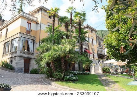 Salo, Italy - August 8, 2018: Tourists Sitting At Villa Laurin And Palm Trees At Lake Garda. The Min