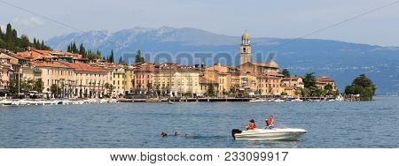 Salo, Italy - August 8, 2018: Townscape Of Salo And Tourists On A Boat With Mountain Panorama At Lak
