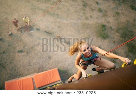 Beautiful Young Strong Woman Climbing On Rock Artificial Wall In Summer, Top View. Climber Insured O