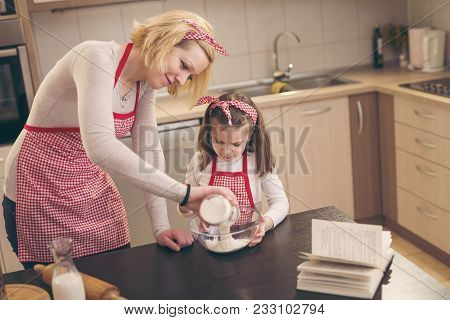 Mother And Daughter Baking Dough In The Kitchen; Mother Adding Flour From A Jar While Daughter Stiri