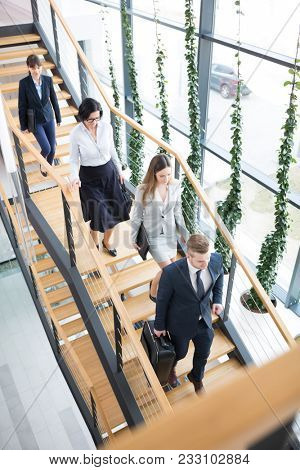 High angle view of male and female business executives moving downstairs in modern office
