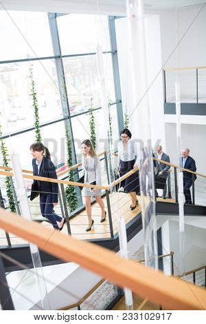 High angle view of business executives climbing stairs in modern office