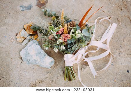 Rustic Wedding Bouquet With Pink Ribbons On The Sand, On The Beach. Close-up. Artwork, Grain. Outdoo