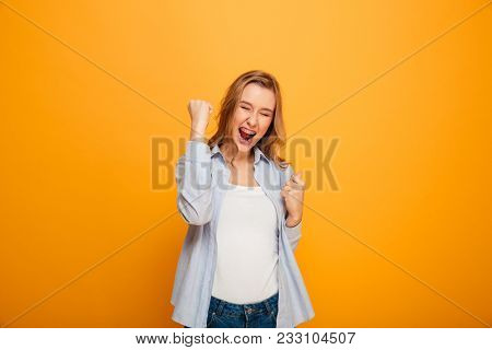 Portrait of successful woman wearing braces yelling and clenching fists, acting like winner or lucky person isolated over yellow background