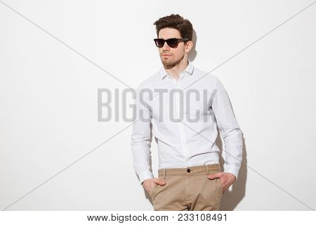 Portrait of fashionable unshaved man dressed in shirt and sunglasses posing on camera with hands in pockets over white background with shadow