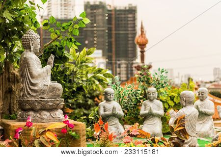 Small Garden With Buddism. Contrast Between Modernity And Tradition.