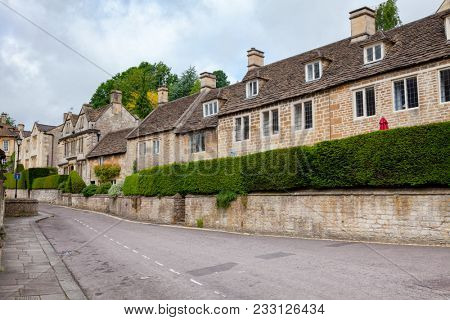 Old slate roof houses decorated with square shaped topiary green shrubs in Bradford on Avon, a town and civil parish in West Wiltshire, Southwest England, UK