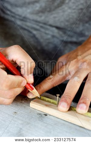 closeup of a young caucasian man making a mark with a carpenter pencil in a wood strip