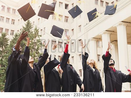 A Group Of Multietnic Students Celebrating Their Graduation By Throwing Caps In The Air. Education,