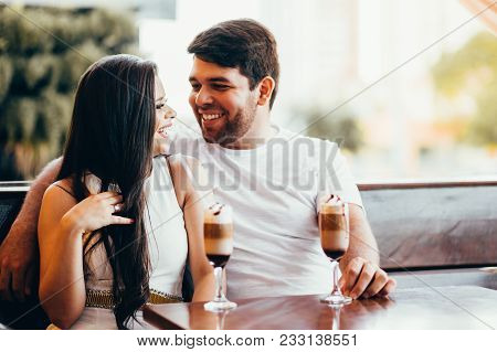 Young Couple In Love Sitting In A Cafe, Drinking Coffee, Having A Conversation And Enjoying The Time