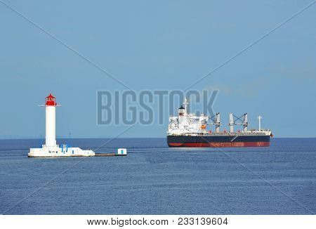Bulk Carrier Near Lighthouse In Odessa, Ukraine