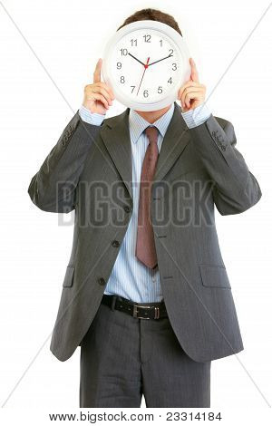 Modern Businessman Holding Clock In Front Of Face