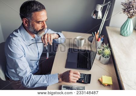 Mature Man Running Small Business From Home Office, Working On Laptop.