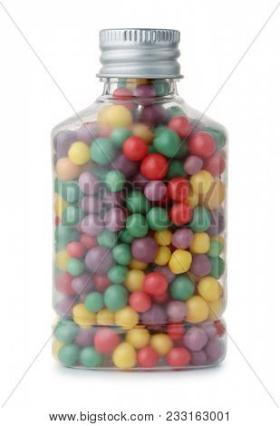Small bottle full of colorful drops candy  isolated on whiite