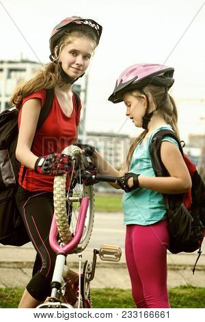 Bicycle tire pumping and repair by child bicyclist. Girl repairing bicycle on road . Kids pump up tire. Children return home from school on bicycles. Tone image. They help children repair bicycles. poster