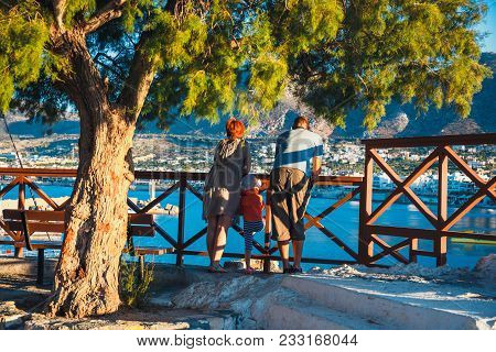 Hersonissos, Crete, June 13, 2017 - Unknown Couple With A Small Child Admire The Sunset In The City