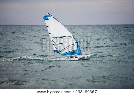 Windsurfer Floating On Board At Sea. Extreme Sports On Vacation.
