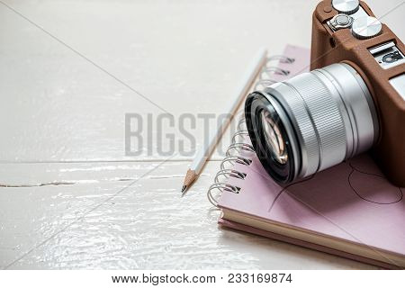 Classic Camera Put On Closed Notebook With Pencil On White Table