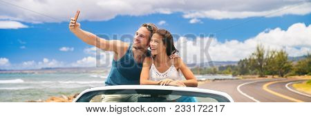 car road trip vacation young people taking selfie photo with phone during summer travel vacation. Tourists couple taking photos on Hawaii in convertible car, with smartphone camera. Banner panorama.