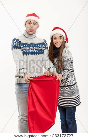 Chirstmas Concept - Young Attractive Couple With Santa Red Bag Celebrating Chirstmas Day. Isolated O