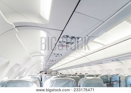 An Empty Passenger Airliner. Commercial Aircraft Cabin With Rows Of Grey Seats Down The Aisle. Vacat