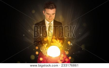 Gorgeous businessman sitting with sparkling magic ball in his lap