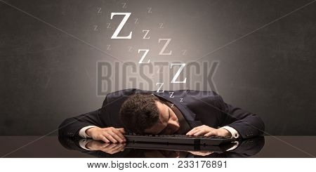 Young businessman fell asleep at the table on his keyboard concept