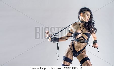 Sensual dominatrix in black underwear with whip, isolated on white, bdsm. Sensual portrait poster