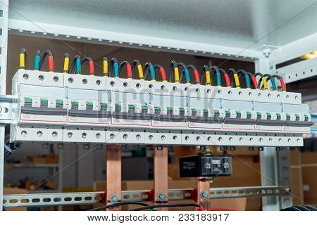 A range of electrical wires or cables are connected to the modular circuit breakers. Black wires are marked in different colors. In the background, the design of the electrical Cabinet with busbars. poster