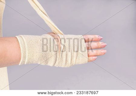 Fractures And Dislocations Concept. Female Hand In A White Bandage. A Useful Preparation For The Pai
