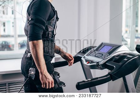 Fit Man In Black Electric Muscle Stimulation Suit For Ems Training Running On Treadmill At Gym